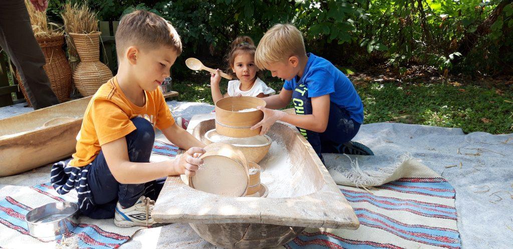 Gyerekek nagy teknőben lisztet szitálnak